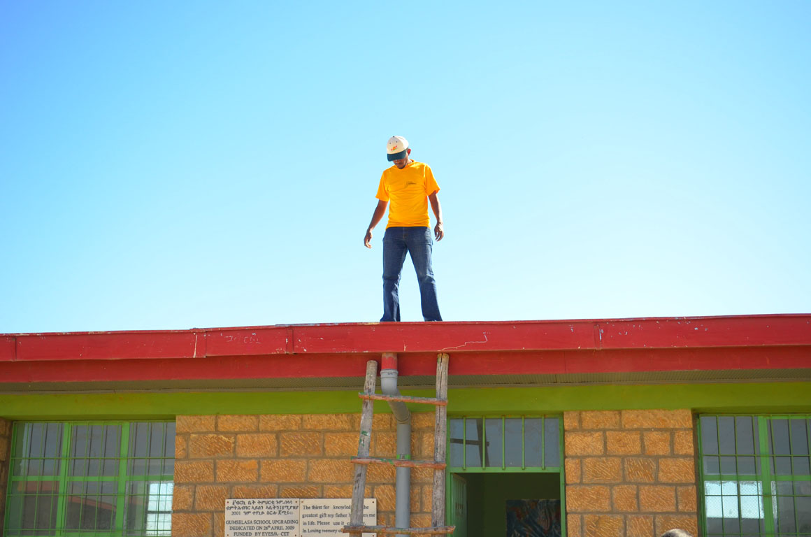 The Solar Energy Foundation technician stands on the roof of the Gum Selasa Elementary School in the Tigray region of Ethiopia.